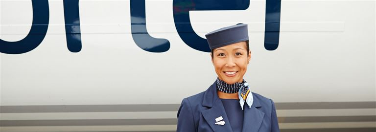 Friendly flight attendant in front of Porter aircraft
